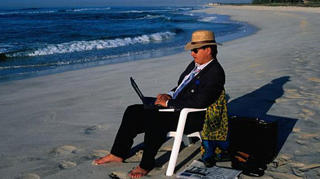 Man typing on a beach